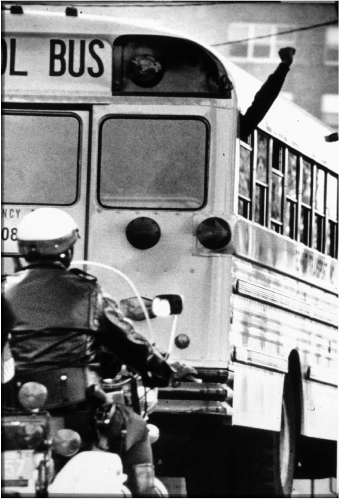 A black student raises a fist while Police  protect school buses in Boston, MA, in 1974 during forced busing to racially integrate schools. Peter Bregg/AP