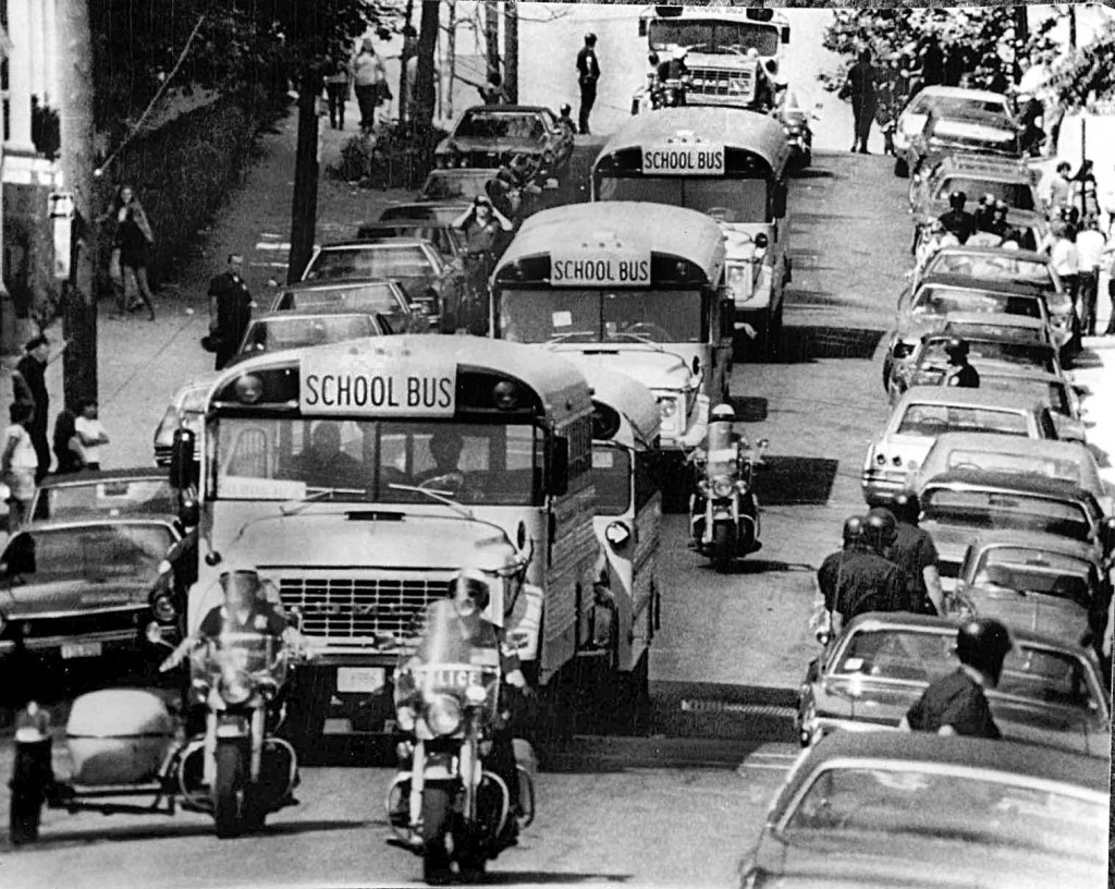 Police  protect school buses in Boston, MA, in 1974 during forced busing to racially integrate schools. Peter Bregg/AP